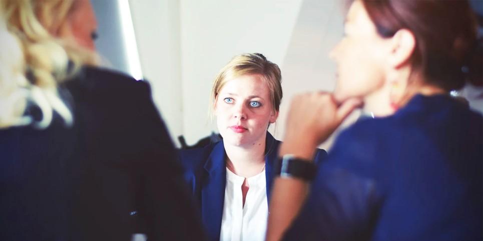 Uma jovem frente a duas mulheres em um ambiente corporativo